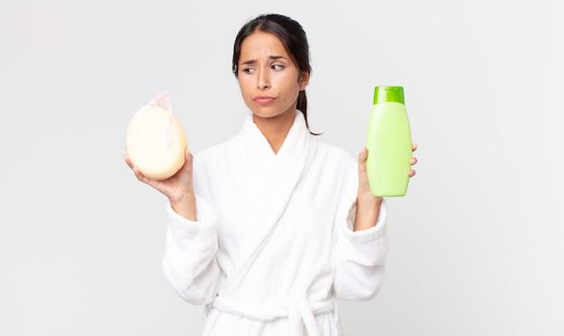 Pretty hispanic woman wearing bathrobe and holding a shampoo and a sponge