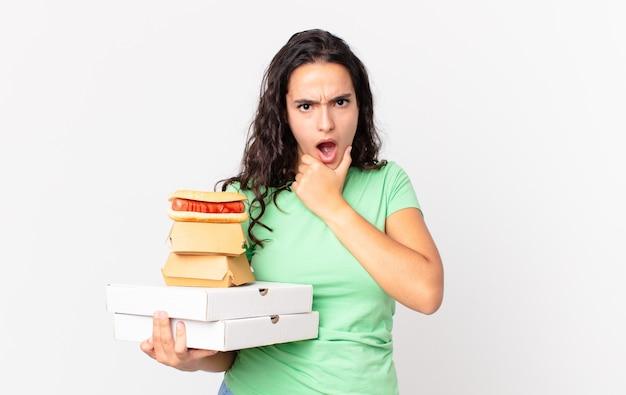 Симпатичная латиноамериканская женщина с широко открытыми глазами и ртом, рукой за подбородок и держащей коробки быстрого питания на вынос