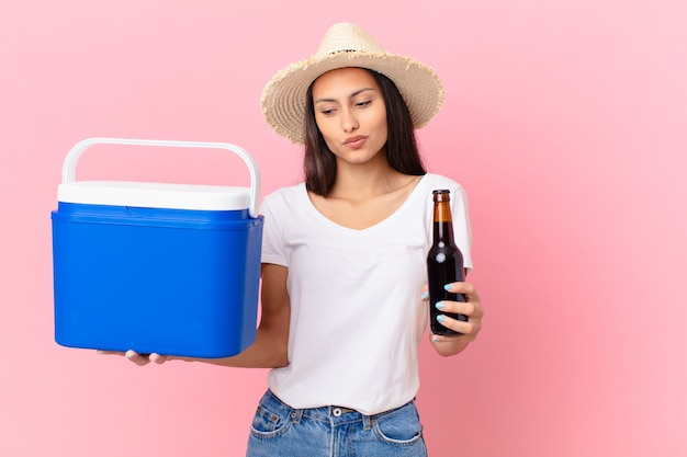 Pretty hispanic woman with a portable freezer and a beer