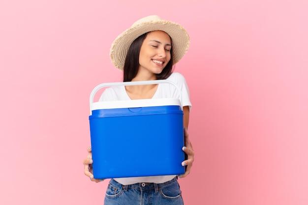 Pretty hispanic woman with a portable freezer