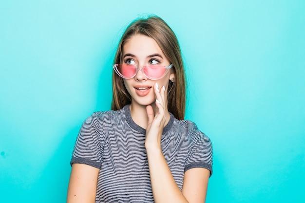 Довольно возбужденная молодая модель в модной футболке, шляпе и прозрачных очках, изолированных на зеленом фоне