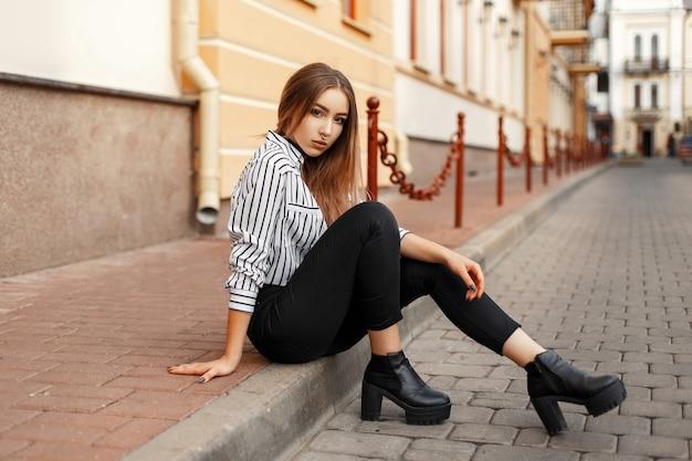 Довольно горячая женщина, сидящая на обочине