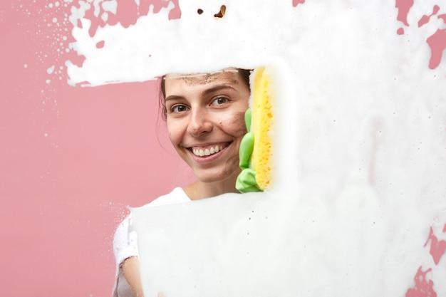 きれいな主婦がスポンジと窓拭きで洗剤を拭いて、笑顔を浮かべて濃厚な泡を拭いて、仕事を楽しんでいます。彼女の家の雑用を自宅でガラスの表面を掃除して幸せなかわいい女