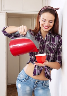 Pretty housewife girl pours water into cup