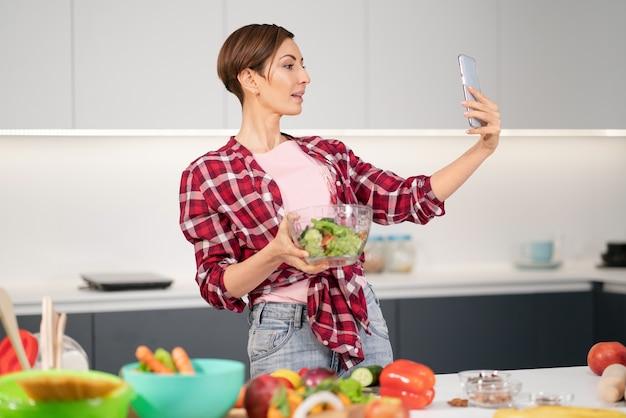 Красивая домохозяйка делает селфи или делает видеозвонок с помощью смартфона во время приготовления свежего салата
