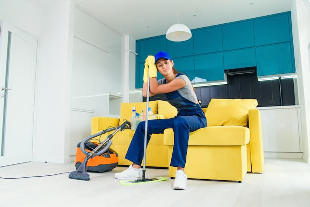 Pretty housewife tired of cleaning sits on the couch and leans to the mop after finish washing the floor.