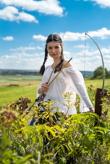 Pretty hunter girl shooting bow and arrow  in the grassland
