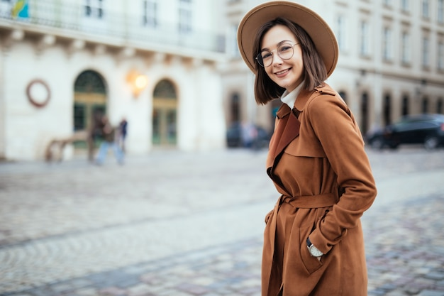 Довольно в современном коричневом пальто позирует на улице в центре города