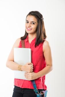 白い背景の上に孤立して立って、バッグとラップトップコンピューターを使用または保持しているかなりインドのアジアの女子大生