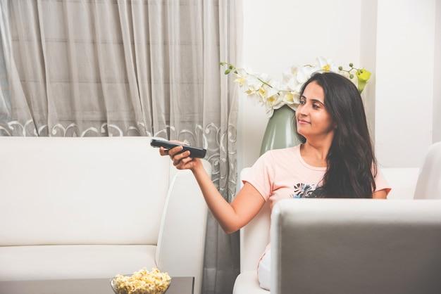 ソファに座ってテレビやテレビを見たり、自宅でリモコンを使用しているかなりインドのアジアの女性