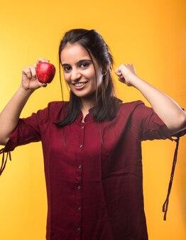 白または黄色の背景の上に孤立して立って、新鮮なリンゴの果実を保持または食べるかなりインドのアジアの若い女の子