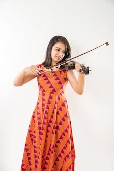 白い背景に対してバイオリンを演奏するかなりインドのアジアの若い女の子のミュージシャン