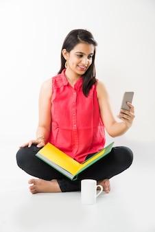 Довольно индийская азиатская молодая девушка, использующая телефон cel или смартфон во время учебы, на белом фоне