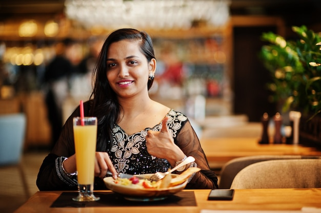 Pretty indian girl in black saree dress posed at restaurant, sitting at table with juice and salad. show thumb up.