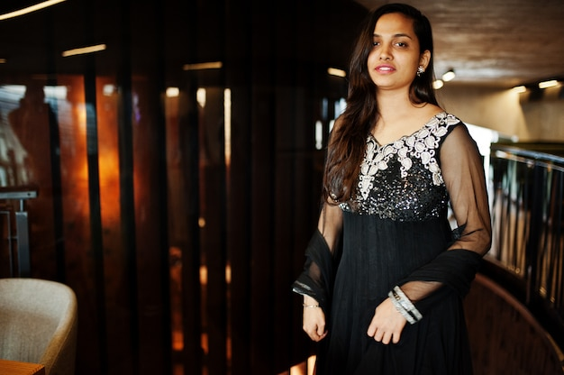 Pretty indian girl in black saree dress posed at restaurant.