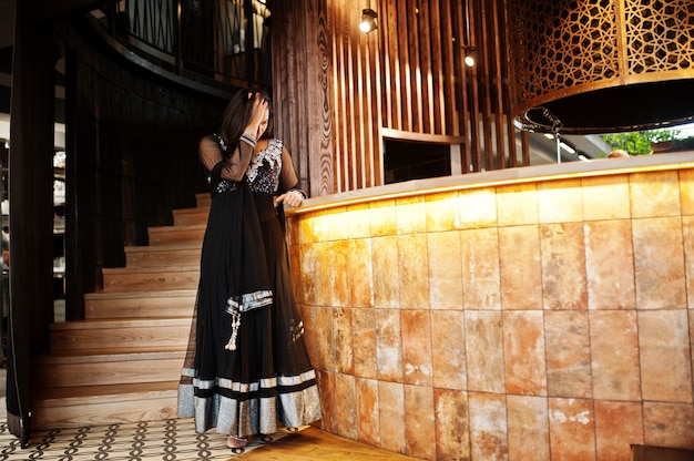 レストランでポーズをとって黒サリードレスでかなりインドの少女。