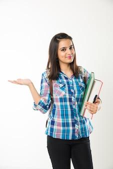 白い背景の上に孤立して立っている間本とバッグを保持しているかなりインドまたはアジアの若い女子大生