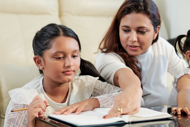 Pretty indian woman explaining difficult topic to her teenage daughter who is studying at home due to coronavirus pandemic