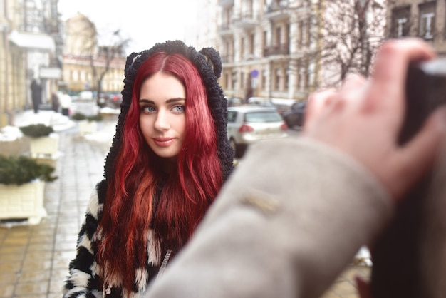 A pretty informal girl with red hair poses and looks at the camera while her friend takes her picture.