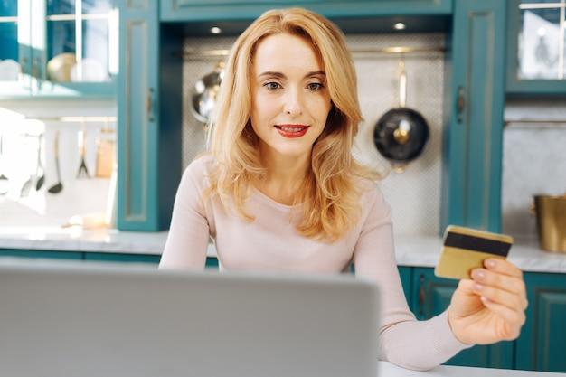カードを持って、キッチンに座ってラップトップで作業しているかなりインスピレーションを得た金髪の若い女性