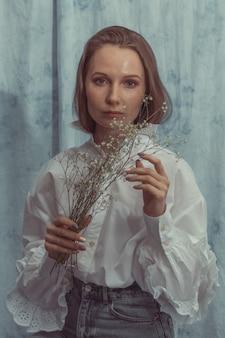 白いブラウスとブルージーンズのドライフラワーの束でポーズかなりインテリジェントな女の子