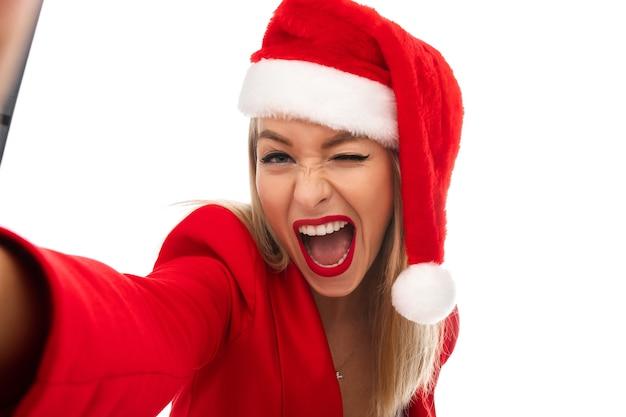 Довольно веселая белокурая кавказская женщина в красной шляпе санта-клауса и куртке, прищурившись, с открытым ртом, делая селфи. студия выстрел изолирует на белом.