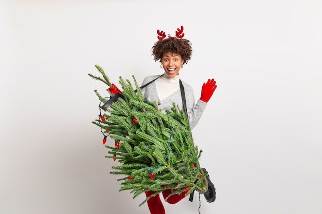 Pretty joyful afro american teenage girl raises hand and leg dances carefree holds fir tree as if musical intstrument pretends being professional guitarist wears christmas costume has fun on party