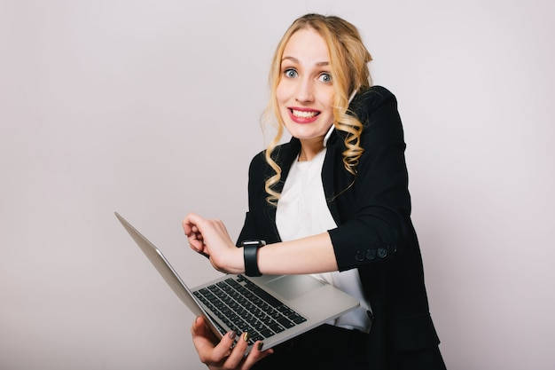 Pretty joyful blonde businesswoman with laptop talking on phone isolated. wearing office suit, stylish, fashionable, being busy, smiling, true emotions