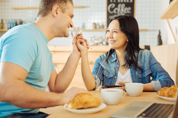 Pretty joyful dark-haired woman and a handsome smiling blond man sitting at the table in a cafe and listening to music and having coffee