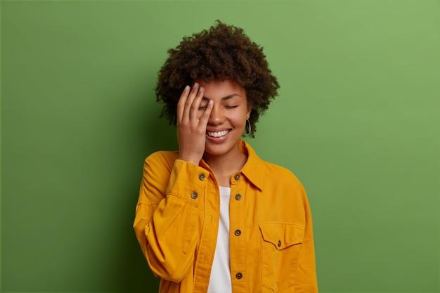Довольно радостная темнокожая женщина держит руку на лице, смеется над смешной шуткой, закрывает глаза от радости, выражает положительные эмоции, носит модную желтую куртку, позирует в помещении над зеленой стеной.