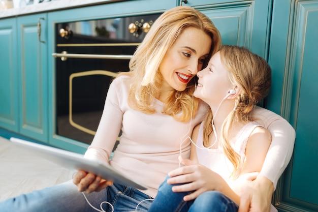 Довольно радостные светловолосые мать и дочь улыбаются и сидят на полу на кухне, слушают музыку и обнимаются