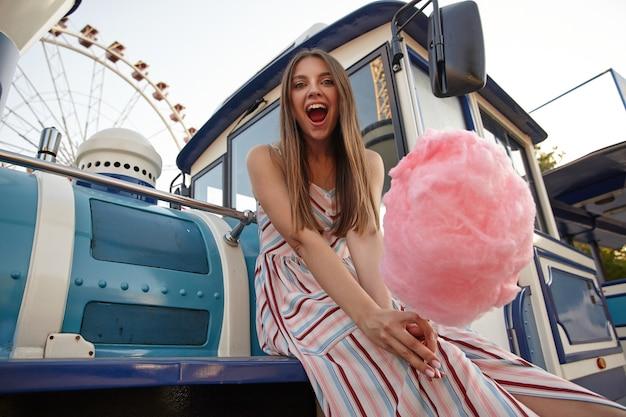 긴 머리가 놀이 공원을 통해 증기 기관차에 앉아 손에 솜사탕을 들고 넓은 입으로 유쾌하게보고있는 꽤 즐거운 여성