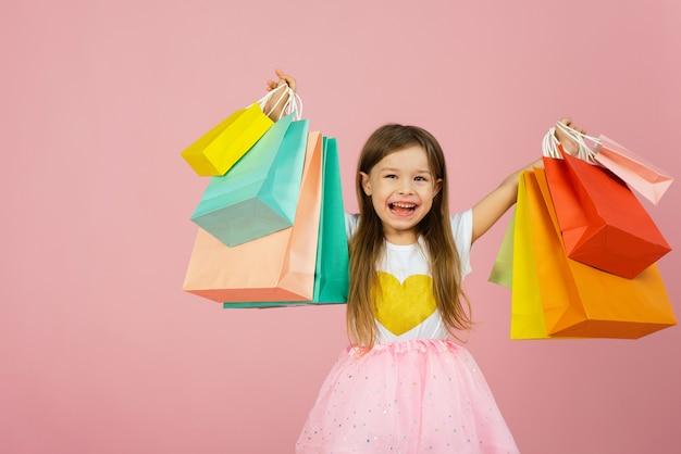 カラフルなパッケージで歩く長いブロンドの髪のチュールスカートのかなり楽しい若い女の子