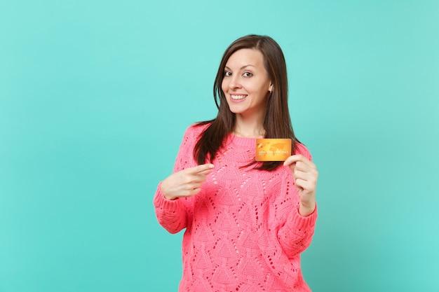 파란색 청록색 벽 배경 스튜디오 초상화에 격리된 손에 신용 카드에 검지 손가락을 가리키는 니트 핑크 스웨터에 꽤 즐거운 젊은 여성. 사람들이 라이프 스타일 개념입니다. 복사 공간을 비웃습니다.