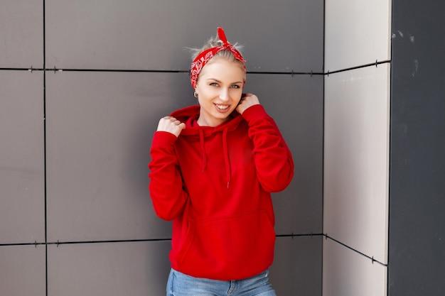빈티지 두건이 달린 빨간 스웨터에 아름다운 미소로 꽤 즐거운 젊은 여성이 따뜻한 여름날에 회색 벽 근처에 서 있습니다.