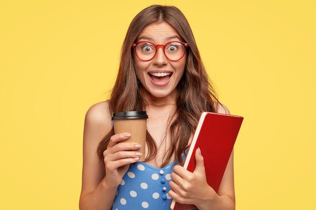 黄色い壁に向かってポーズをとって眼鏡をかけてかなり楽しい若い女性