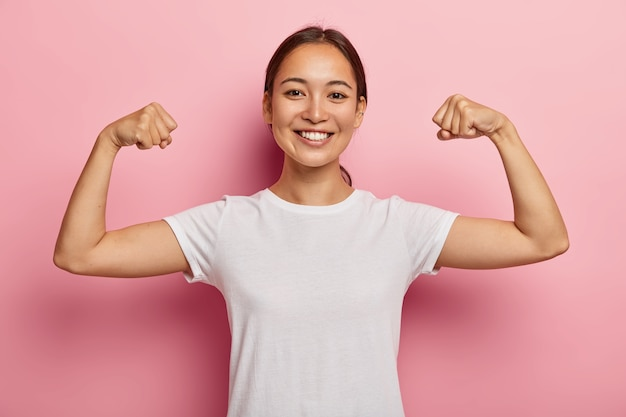 Симпатичная корейская модель поддерживает форму и здоровье, поднимает руки и демонстрирует мышцы, гордится своими достижениями в тренажерном зале, широко улыбается, одета в белую повседневную одежду, позирует в помещении показывает настоящую силу