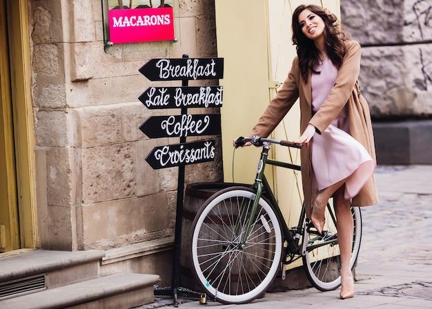 La bella signora in cappotto beige si siede sulla bicicletta prima di un caffè
