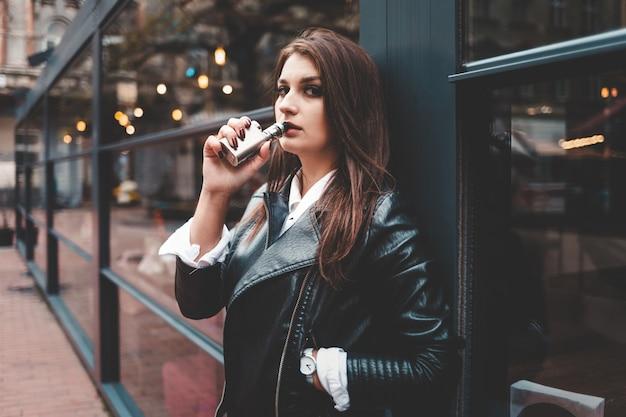 Pretty lady in a black leather jacket smokes electronic cigarette near glass windows
