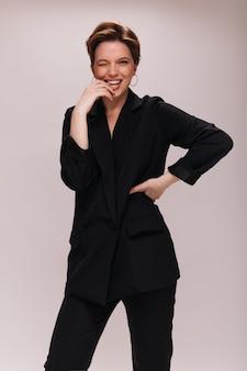 Bella signora in abito nero strizza l'occhio su sfondo isolato. affascinante giovane donna in giacca scura e pantaloni che ride su sfondo bianco