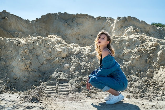 Pretty lady in blue overalls walks in a sand quarry, active way