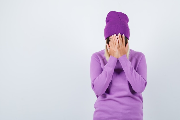 Pretty lady covering face with hands in sweater, beanie and looking depressed , front view.