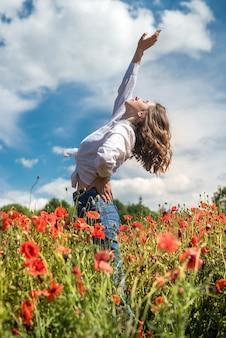 예쁜 아가씨는 화창한 날 붉은 양귀비 밭에서 자유 시간을 즐깁니다. 건강한 생활