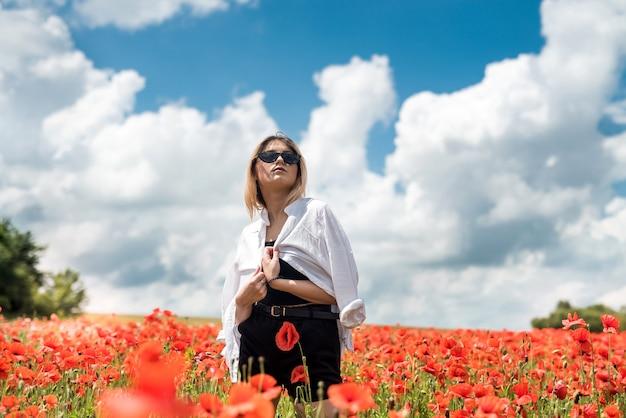 예쁜 아가씨는 빨간 양 귀 비 필드, 화창한 날에서 자유 시간을 즐깁니다.