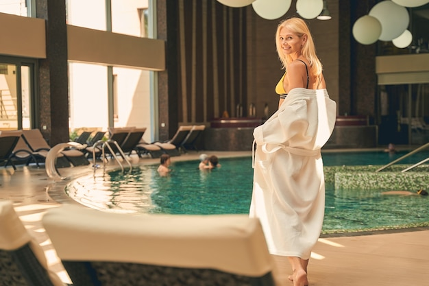 Pretty lady having fun and posing while relaxing near the swimming pool in luxury hotel