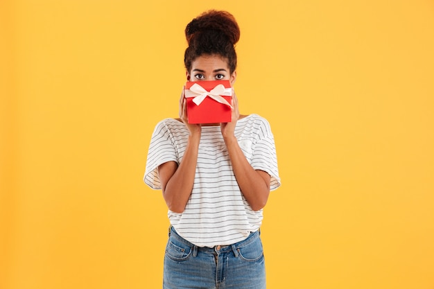 Pretty lady hiding face with present isolated