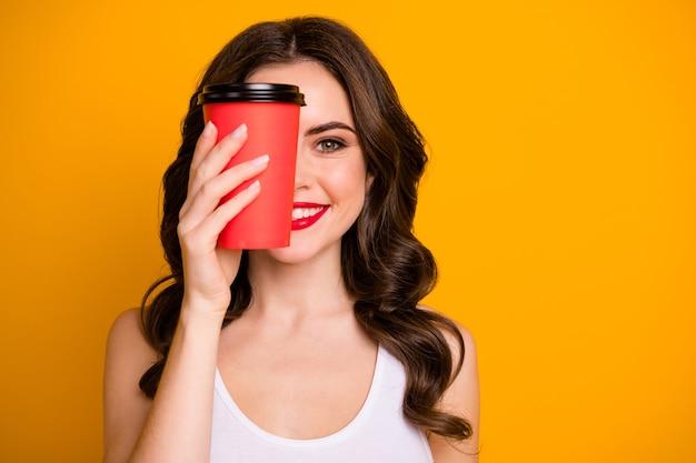 Симпатичная леди держит бумажный стаканчик на вынос горячий кофе, пряча половину лица