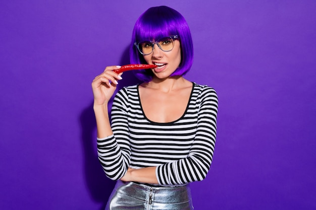 Красивая дама держит во рту красный перец чили. бесстрашный человек любит пряную еду носить характеристики полосатый пуловер изолированный фиолетовый фон