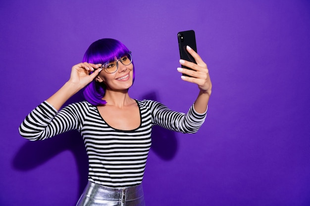Pretty lady hold telephone taking selfies speaking skype best friend wear specs striped pullover isolated purple background