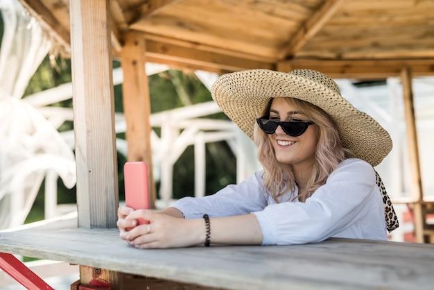 예쁜 아가씨 셀을 들고 뜨거운 여름 날에 나무 전망대 근처에서 셀카를하고. 휴식을 취하고 자연을 즐기다